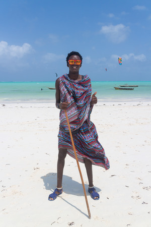 Traditonaly dressed black man with funny sunglasses on Paje beach. Maasai warrior on picture perfect tropical sandy beach on Zanzibar, Tanzania, East Africa. Stock Photo