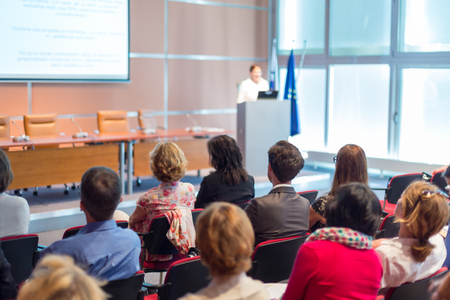 Business and entrepreneurship symposium. Speaker giving a talk at business meeting. Audience in conference hall. Rear view of unrecognized participant in audience. Stok Fotoğraf