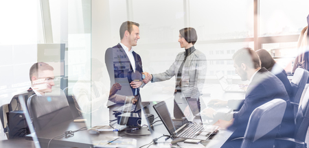 Sealing a deal. Business people shaking hands, finishing up meeting in corporate office. Businessmen working on laptop seen in glass reflection. Business and entrepreneurship concept. Stock Photo