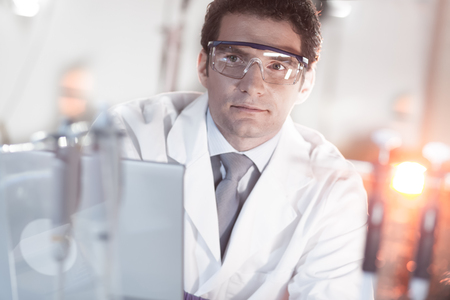 Portrait of a confident male engineer in his working environment. Science and technology concept.