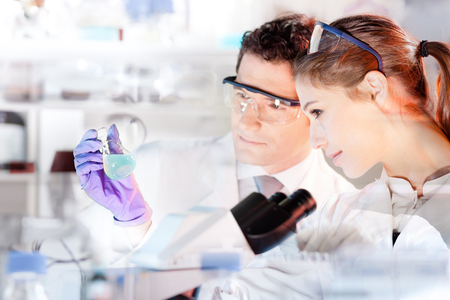 doctoral: Chemical laboratory. Attractive young PhD student and her post doctoral supervisor scientist observing the blue indicator color shift after the solution  destillation. Stock Photo
