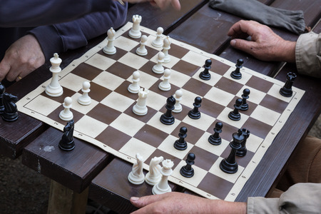 Close up of hands of senior men playing chess sitting at the wooden desk opposite each other. Banco de Imagens