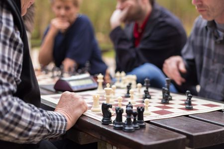 chess board: Close up of hands of senior men playing chess sitting at the wooden desk opposite each other. Stock Photo