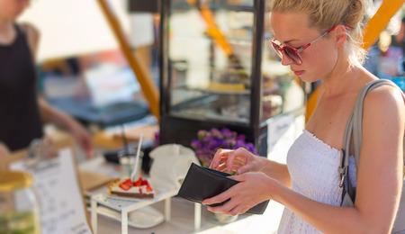 cash money: Hermosa dama rubia caucásica vistiendo vestido de verano blanco comprar comida recién preparada en un festival de comida de calle local. Evento urbano internacional de la cocina en Ljubljana, Eslovenia, en verano.