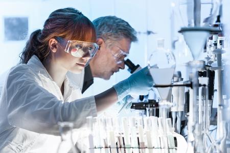 Pesquisadores de saúde trabalhando no laboratório de ciências da vida. O cientista fêmea novo da pesquisa e o supervisor masculino superior que preparam e que analisam o microscópio deslizam no laboratório de pesquisa. Foto de archivo