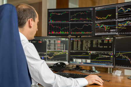Rear view of stock trader looking and analyzing stock data at multiple computer screens.