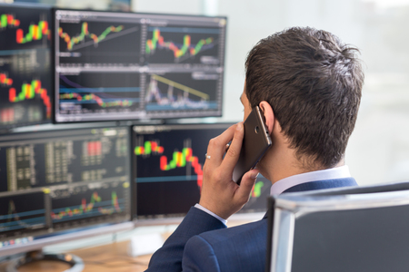 analyses: Over the shoulder view of and stock broker trading online while accepting orders by phone. Multiple computer screens ful of charts and data analyses in background.