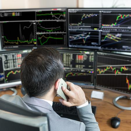 Ber die Schulter Blick und Börsenmakler Online-Handel, während Bestellungen per Telefon angenommen werden. Mehrere Computerbildschirme voller Diagramme und Datenanalysen im Hintergrund. Standard-Bild - 79106287