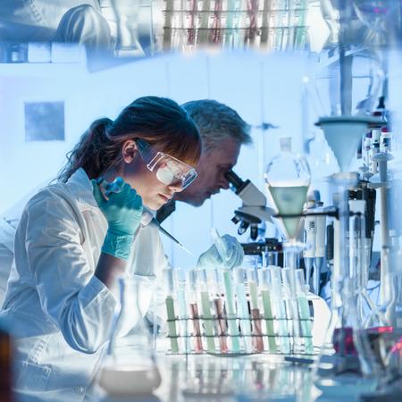 Ricercatori di assistenza sanitaria che lavorano nel laboratorio della scienza della vita. Giovane scienziato di ricerca femminile e supervisore maschio senior preparando e analizzando diapositive a microscopio nel laboratorio di ricerca. Archivio Fotografico - 79106280
