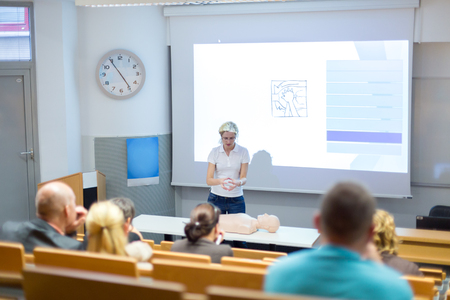 Instructor teaching first aid cardiopulmonary resuscitation course and use of automated external defibrillator on voluntary public workshop for senior people. Stock Photo