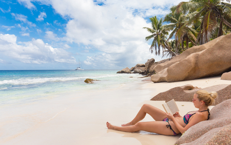 la digue: Woman reading book on perfect tropical beach of Anse Patates on La Digue Island, Seychelles. Summer vacations on picture perfect tropical beach concept.