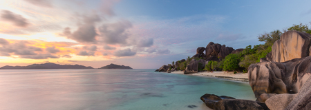 Beautifully shaped granite boulders and a dramatic sunset at picture perfect tropical Anse Source dArgent beach, La Digue island, Seychelles. Stock Photo