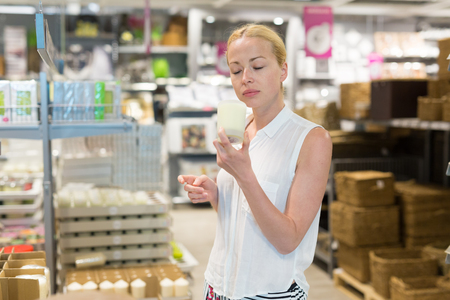 dimensions: Beautiful young caucasian woman choosing the right item for her apartment in a modern home decor furnishings store. Shopping in retail store.