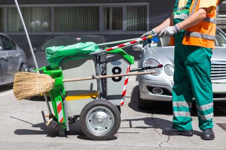 Arbeitskraft der Reinigungsfirma in der grünen Uniform mit Mülltonne und einem Besen. Gebrauchsdienstleistungsunternehmensmannarbeiter der Gemeinde, die Stadtstraßen fegt. Standard-Bild