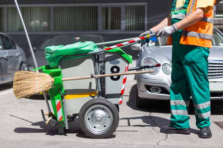 Worker of cleaning company in green uniform with garbage bin and a broom. Utility service company men worker of municipality sweeping city streets.