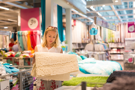shopper: Pretty, young woman choosing the right item for her apartment in a modern home decor furnishings store.