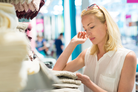 Pretty, young woman choosing the right towel for her apartment in a modern home decor furnishings store.