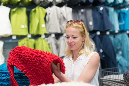 Pretty, young woman choosing the right item for her apartment in a modern home decor furnishings store.
