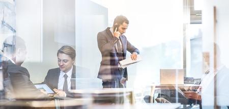 Geschäftsmannexekutive, die am Handy im modernen Unternehmensamt, die Finanzzeitung überprüfend, die Zeit auf wriswatch überprüft. Glasreflexion von den Geschäftsleuten, die im Büro sich treffen. Zeit ist Geld.