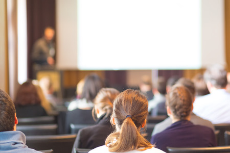 faculty: Speaker at Business Conference and Presentation. Audience in the conference hall. Business and Entrepreneurship. Copy space on white screen. Stock Photo