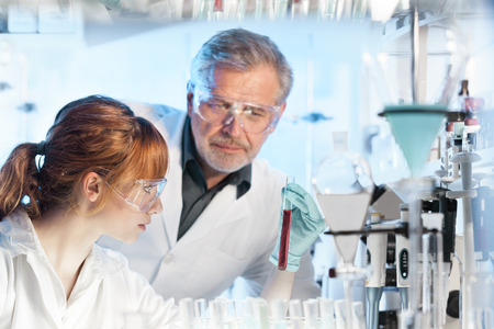 Health care researchers working in life science laboratory. Young female research scientist and senior male supervisor observing red indicator color shift in tube due to change of pH in solution . photo