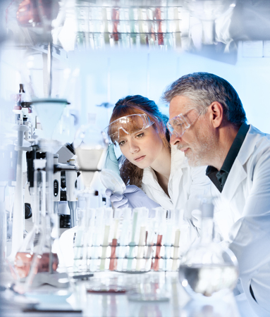 Attractive young female scientist and her senior male supervisor looking at the cell colony grown in the petri dish in the life science research laboratory. photo