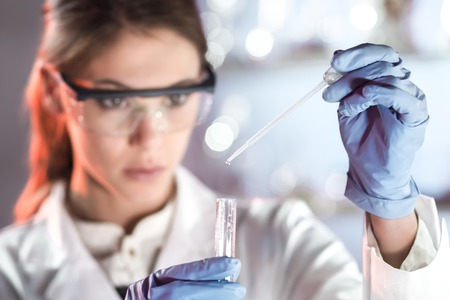Life scientists researching in laboratory. Focused female life science professional pipetting solution into the glass cuvette. Lens focus on researchers eyes. Healthcare and biotechnology concept. photo