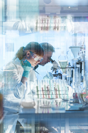 Health care researchers working in life science laboratory. Young female research scientist and senior male supervisor preparing and analyzing microscope slides in research lab. photo