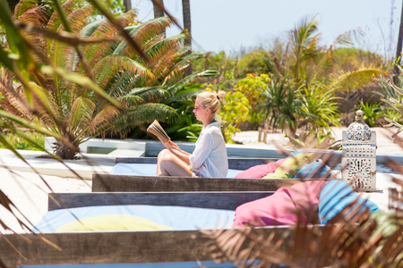 Fancy lady in white beach tunic reading book and relaxing by poolside of luxury spa resort set in lush tropical garden. Relaxation and wellbeing concept.