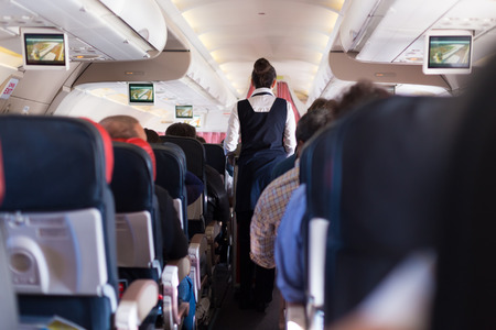 Interior of commercial airplane with passengers on seats during flight. Stewardess in dark blue uniform walking the aisle. Horizontal composition. Banco de Imagens - 84332555