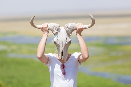 kenya: Woman holding a white wildebeest skull wearing it like a mask in nature on african wildlife safari, Amboseli national park, Kenya.