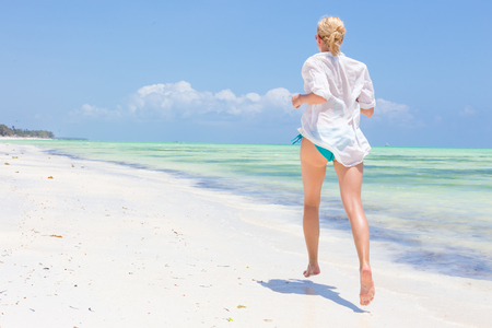 Happy woman having fun, enjoying summer, running joyfully on tropical beach. Beautiful caucasian model wearing white beach tunic on vacations on picture perfect Paje beach, Zanzibar, Tanzania. 版權商用圖片