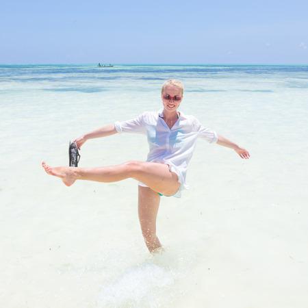Young slim fit woman wearing white beach tunic making water splashes on white sandy beach. Vacation concept. Summer mood. Tropical beach setting. Paje, Zanzibar, Tanzania.