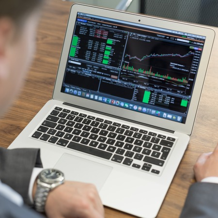 Corporate businessman analyzing economic data on laptop computer. Mans hands on notebook computer, business person at workplace. Banque d'images