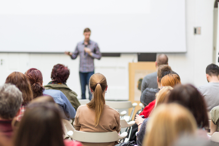 Male speaker giving presentation in lecture hall at university workshop. Audience in conference hall. Rear view of unrecognized participant in audience. Scientific conference event. Stock Photo - 82981796