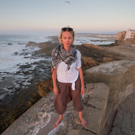 女性旅行者は、エッサウィラ、モロッコの都市要塞壁に裸足で立っています。旅行ライフ スタイルの冒険概念。アクティブな休暇。一人の女性の世 写真素材
