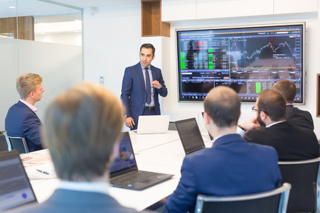 Businessman giving a talk in conference room. Business executive delivering presentation to business partners during business meeting. Corporate business concept. Stockfoto