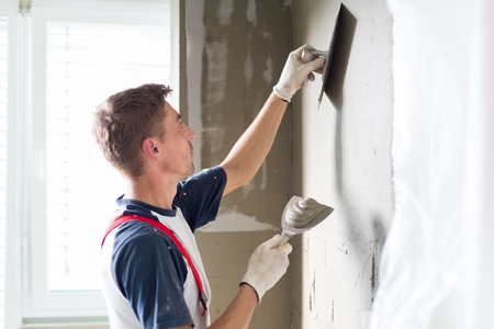 Thirty years old manual worker with wall plastering tools renovating house. Plasterer renovating indoor walls and ceilings with float and plaster. Stockfoto