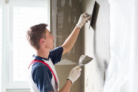 Dreißig Jahre alt Arbeiter mit Wandverputz Werkzeuge Renovierung Haus. Gipser Renovierung Innenwände und Decken mit Schwimmer und Gips. Standard-Bild