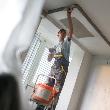 Bouwvakker draagt werknemer overall met muur stukadoors gereedschappen renovatie appartementencomplex. Stukadoor renovatie van binnenmuren en plafonds met vlotter en gips. Bouw afwerking. Stockfoto