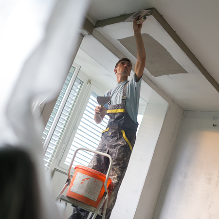 plasterer: Construction worker wearing worker overall with wall plastering tools renovating apartment house. Plasterer renovating indoor walls and ceilings with float and plaster. Construction finishing works.