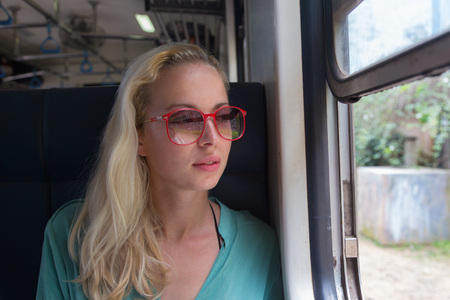 third world: Blonde caucasian woman looking trough old retro blue train window , traveling by train in third world country.