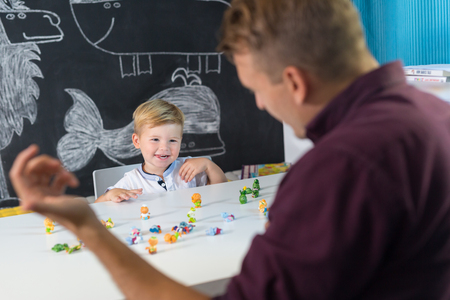 Cute little playfull toddler boy at child therapy session. Private one on one homeschooling with didactic aids. Stock Photo - 86435230