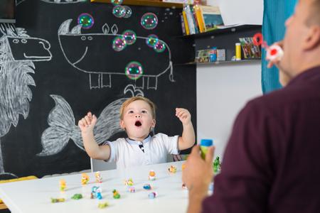 Pequeño niño pequeño lindo del playfull asombró por las burbujas lechosas en la sesión de la terapia del niño. Enseñanza en el hogar privada uno a uno con ayudas didácticas.