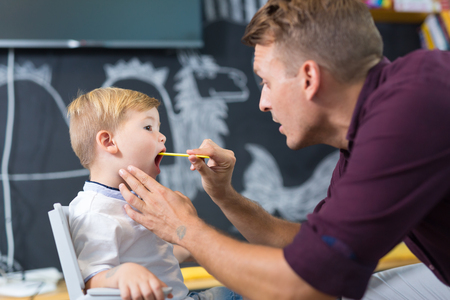 Cute little boy at speech therapist session. Private one on one homeschooling. Stock Photo - 86435233