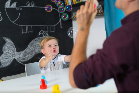 Cute little playfull toddler boy amazed by milky bubbles at child therapy session. Private one on one homeschooling with didactic aids. Stock Photo - 86941899