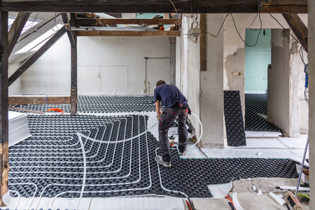 Pipe fitter mounting underfloor heating. Heating system and underfloor heating.