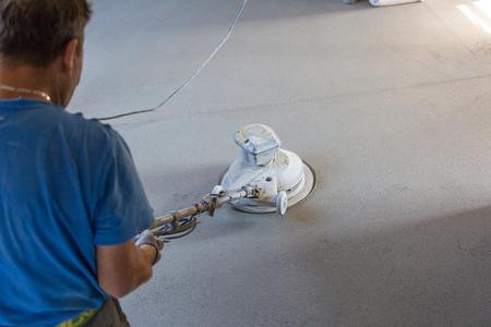 Ouvrier exécutant et polissant le plancher de chape de sable et de ciment. Chape de sol en sable et ciment. Banque d'images - 87395936