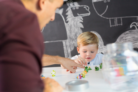 Cute little playfull toddler boy at child therapy session. Private one on one homeschooling with didactic aids. Stock Photo - 87395937