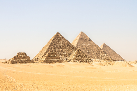 Giza pyramids in Cairo, Egypt. General view of pyramids from the Giza Plateau Three pyramids known as Queens Pyramids on front side. Next in order from left, the Pyramid of Menkaure, Khafre and Chufu